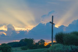 A cross surrounded by sunlight bursting through clouds