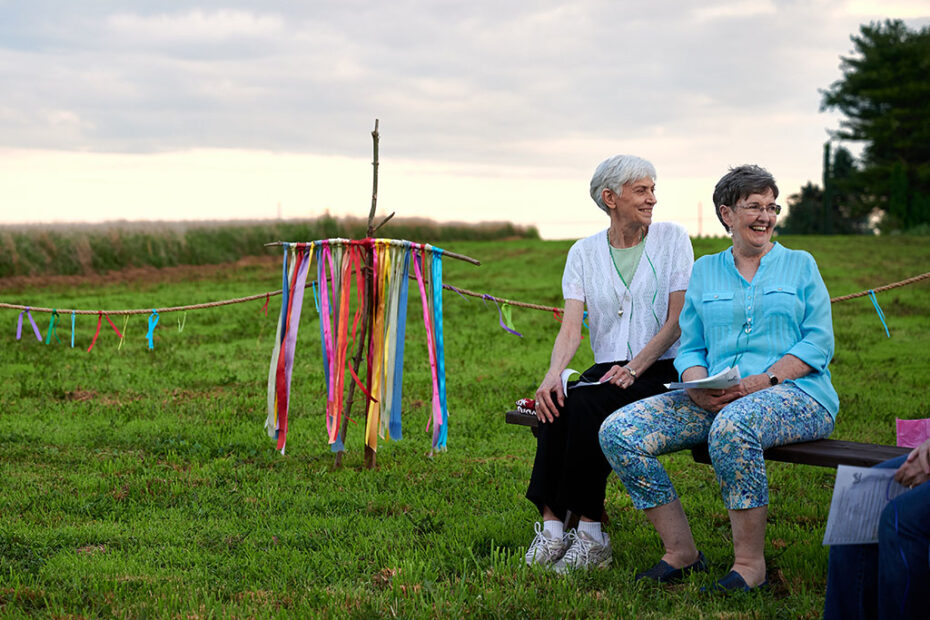 Sisters Dani and Angela laugh in the field of Cornfield chapel next to a cross with multicolored ribbons. Photo by Dave Perry
